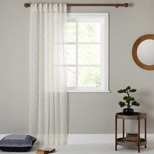 Image of a window with a voile panel hanging to one side