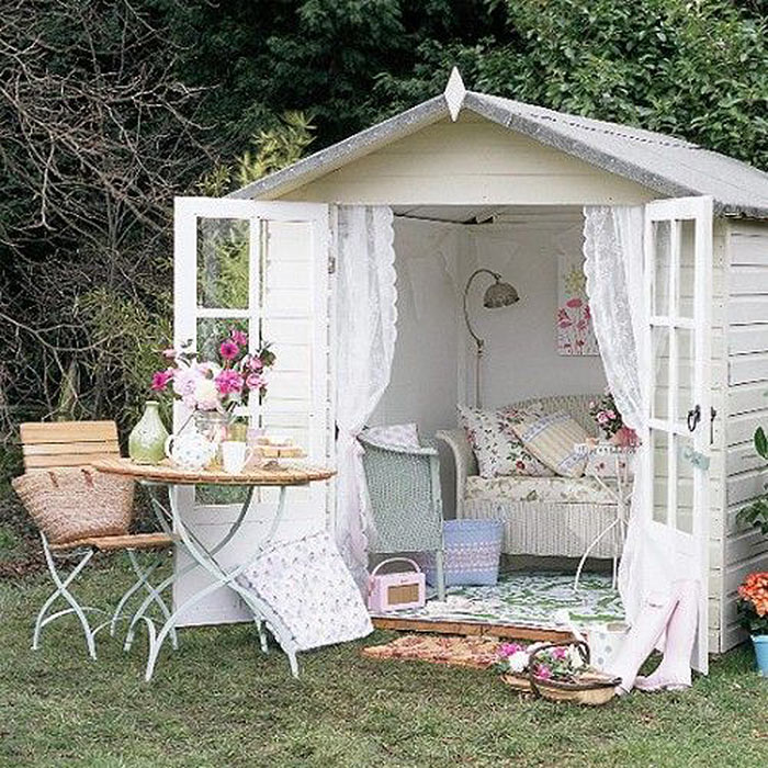 Image of a she shed with interior decorated in pastel and comfy sofa