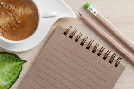 Image of spiral notebook with pens and a cup of coffee