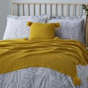 Bed dressed with yellow knitted throw and cushion with pom pom trim