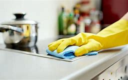 Image of a hand in a rubber gove cleaning a kitchen