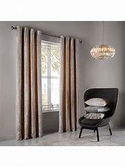 Image of gold coloured floor length curtains with chair with cushions on it
